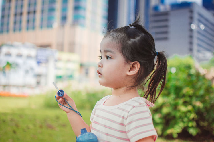 Side view of cute girl holding bubble wand while looking away in park
