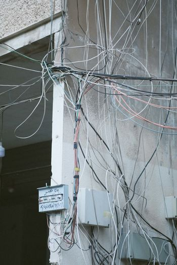Close-up of telephone pole against building