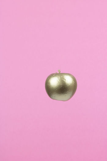 Close-up of apple against pink background