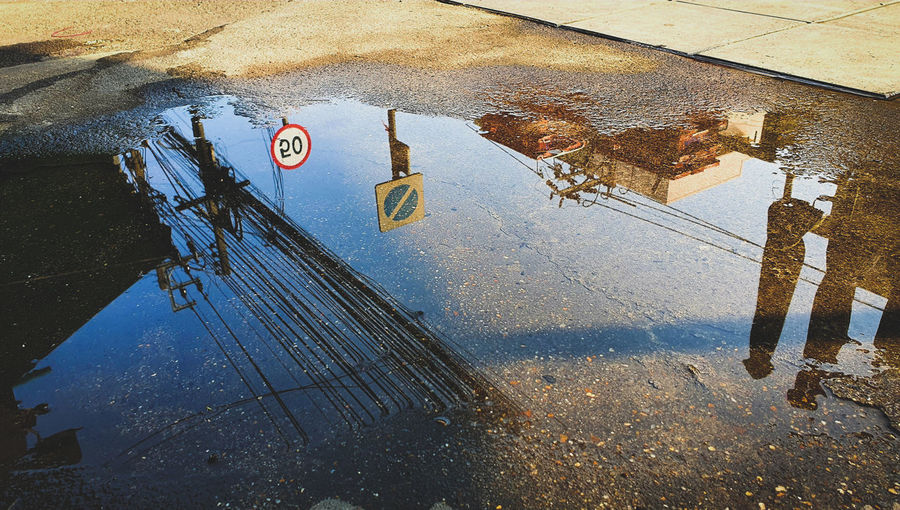 High angle view of road sign on puddle