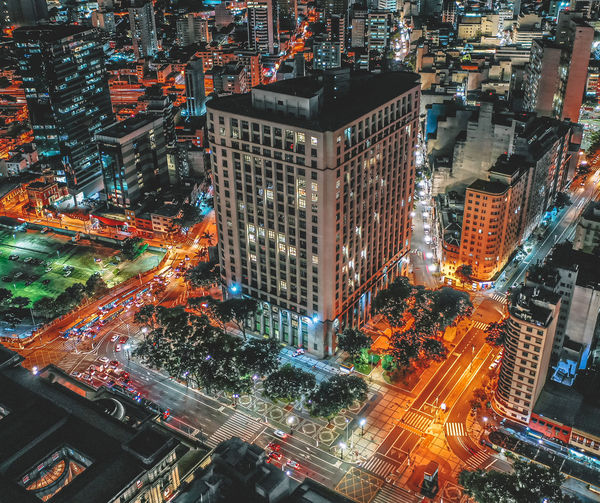 Aerial view of modern buildings in city at dusk