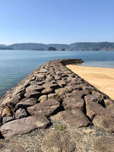 Down By The Sea Scenics Water Tranquil Scene Nature Tranquility Sea Beauty In Nature Rock - Object Mountain Outdoors Day No People Beach Clear Sky Sky Groyne Imari Japan