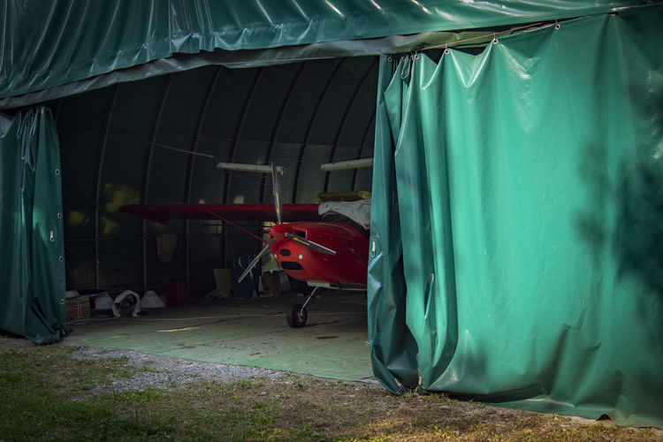 Hangar Abandoned Absence Airplane Architecture Building Built Structure Curtain Day Garage Green Color Metal Mode Of Transportation Nature No People Outdoors Shed Textile Transportation