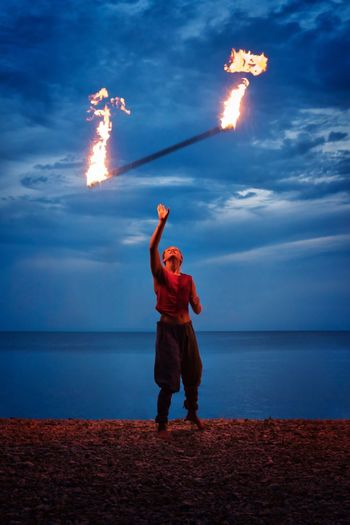 Playing with fire. Performance Young Woman PENTAX K-1 Exceptional Photographs Fire Dancer Art Magic Light And Shadow Fire And Flames Show Street Streetphotography Mideval Girl Juggling Fire Playing With Fire Real People Sea Sky Burning Horizon Over Water Flame Cloud - Sky Standing Leisure Activity Beach