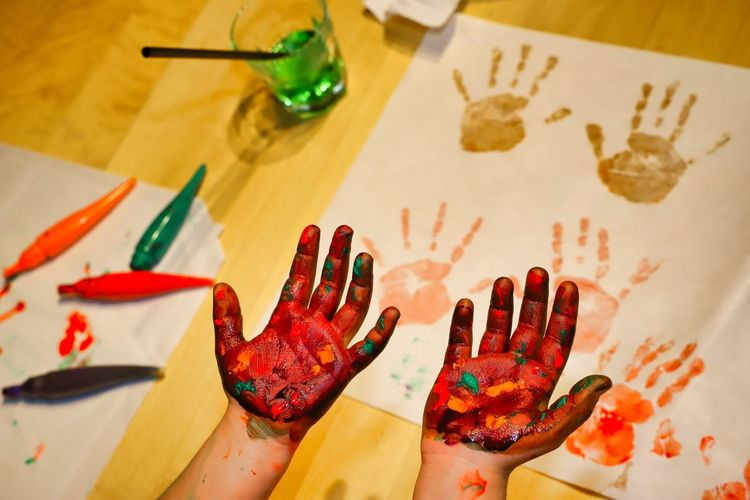 High angle view of messy hands over painting on table