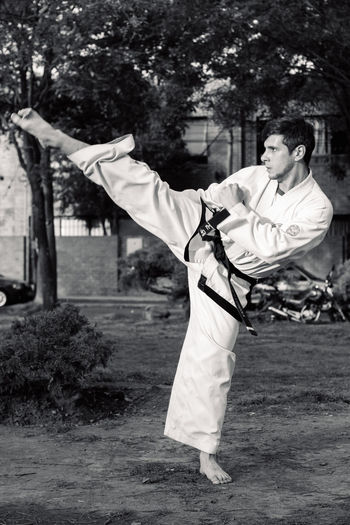 Full length of young man doing karate on field