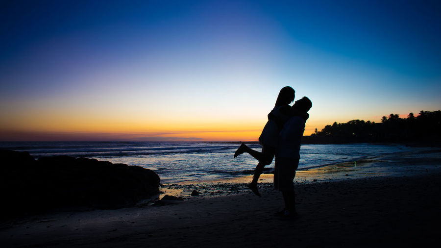 Silhouette couple embracing at beach against sky during sunset