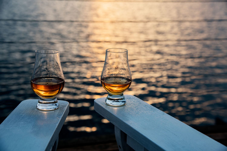 Sipping whiskey seaside Adirondack Chairs Alcohol Beautiful Deck Focus On Foreground Food And Drink Glasses Home Lifestyle Refreshment Relax Scotch Seaside Selective Focus Stemware Still Life Sunset Traditional Traveling Vacation Whiskey Two Is Better Than One