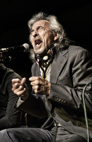 Senior Man Singing Against Black Background