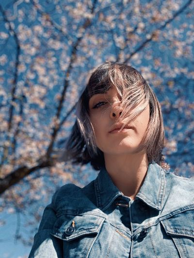 Low angle portrait of young woman with tousled hair in park during spring
