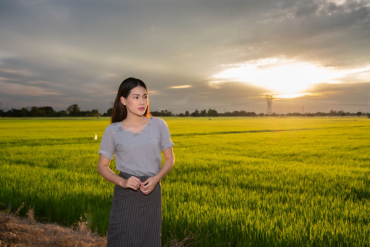Young woman standing on agricultural field against sky during sunset
