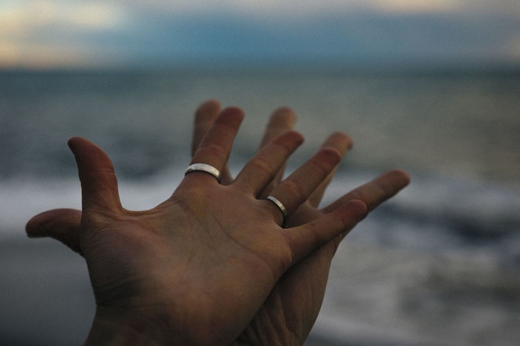 Close-Up Of Human Hands Against Sky
