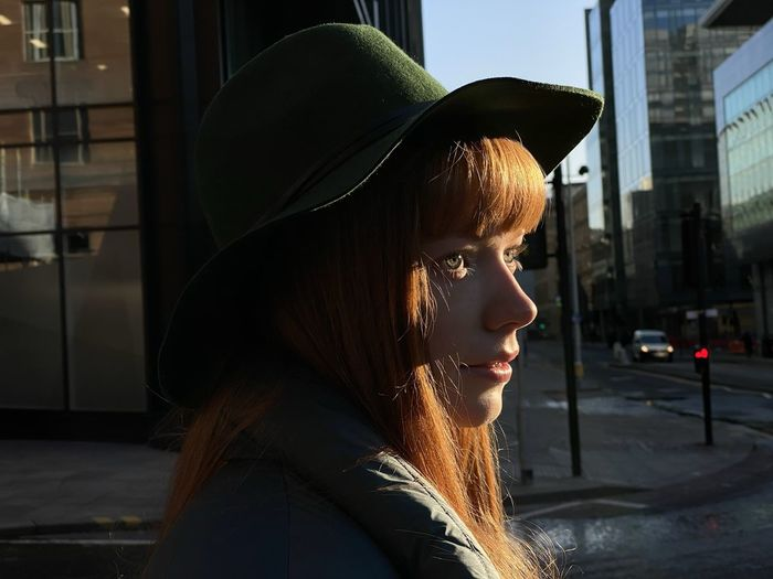 Side view of young woman wearing hat looking away in city