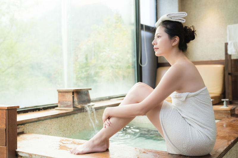 Young Woman Wrapped In Towel Sitting At Swimming Pool