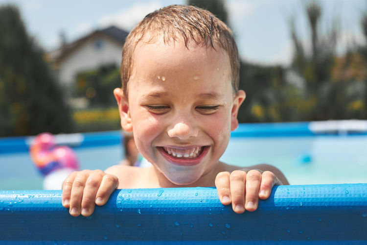 Portrait of happy smiling boy playing in a pool having fun on a summer sunny day