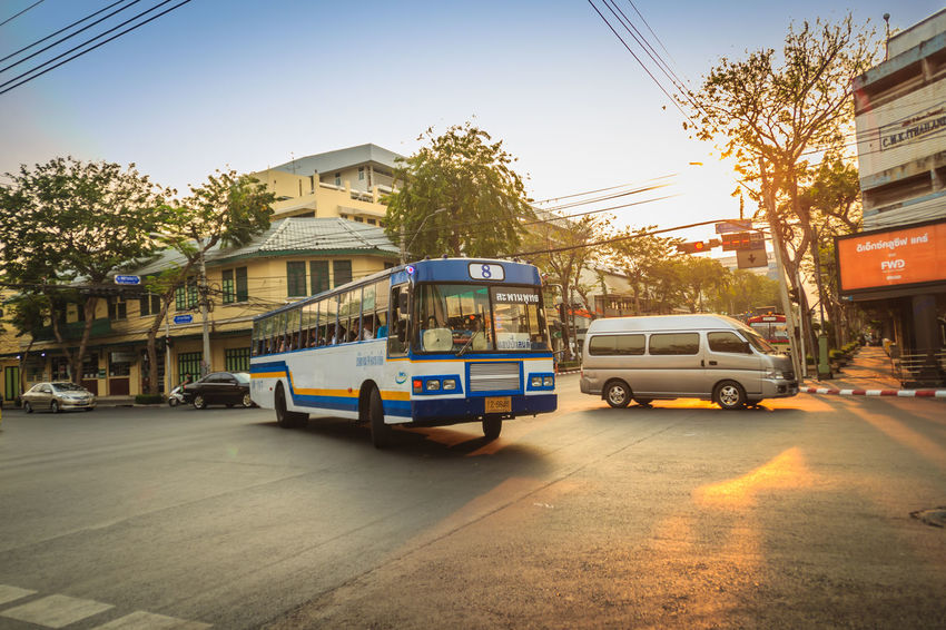 Bangkok, Thailand - March 2, 2017: Local bus and cars in traffic passes through a busy junction during sunset in Bangkok, Thailand. Sunlight Traffic Traffic Jam Traffic Signs Trafficlight Architecture Building Building Exterior Built Structure Car City Day Junctionsquare Land Vehicle Mode Of Transportation Motor Vehicle Nature Outdoors Plant Residential District Road Sky Street Sunbeam Sunlight Sunrise Sunset Sunshine Traffic Arrow Sign Traffic Control Traffic Flow Traffic Light  Traffic Lights Traffic Sign Traffic Signal Trafficjam Trafficlights Transportation Tree
