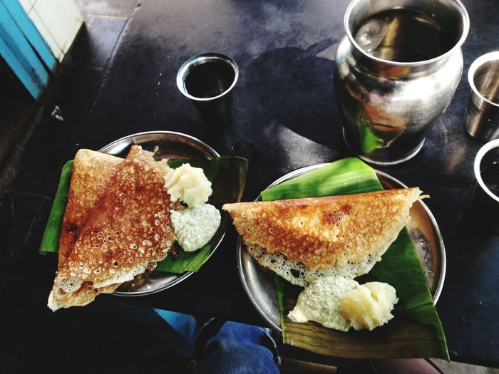 Directly above shot of dosa with coconut sauce and mashed potato on banana leaves
