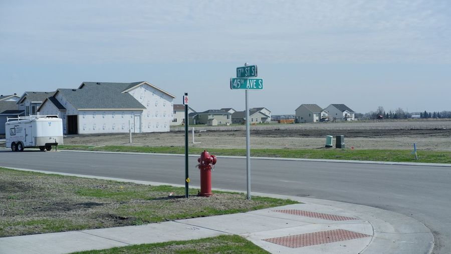 Fire Hydrant By Information Sign On Road By Houses Against Sky