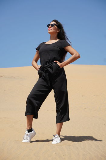 Full length of young woman standing on sand dune