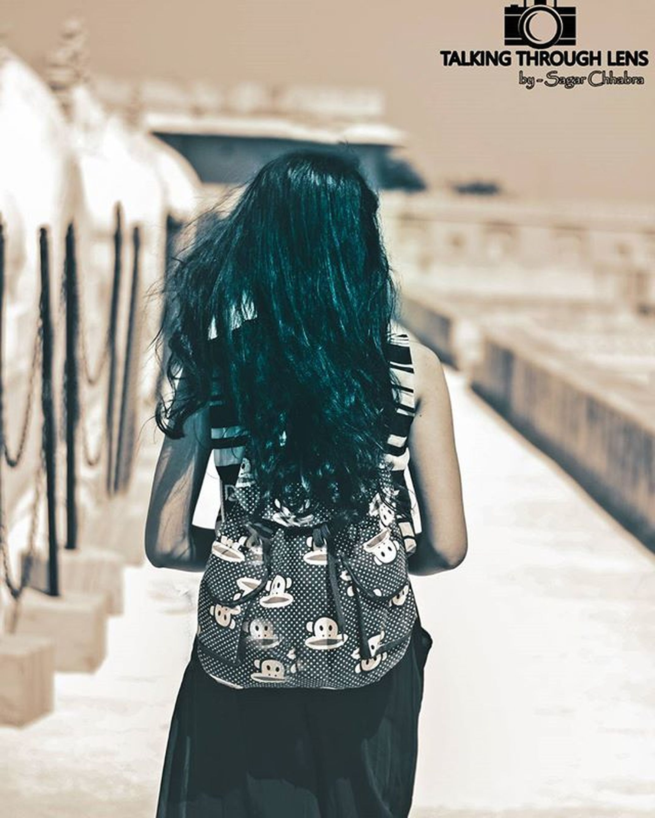 focus on foreground, lifestyles, leisure activity, rear view, person, casual clothing, standing, waist up, holding, long hair, close-up, side view, day, three quarter length, outdoors, part of, men