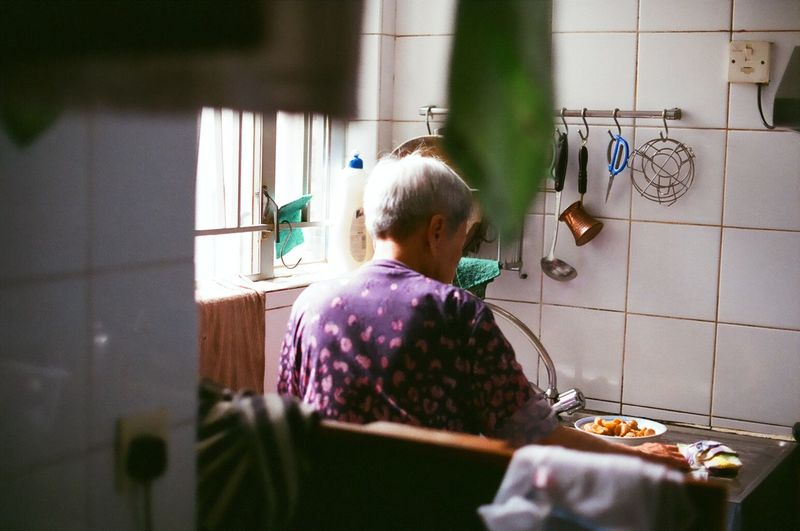 Rear view of woman preparing food in kitchen at home