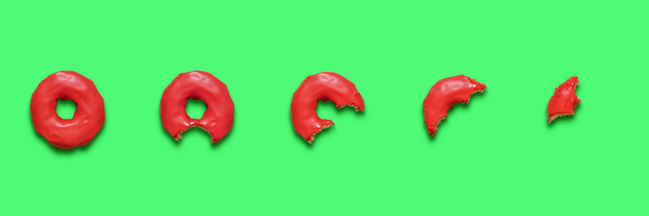 Close-up of red chili peppers over green background