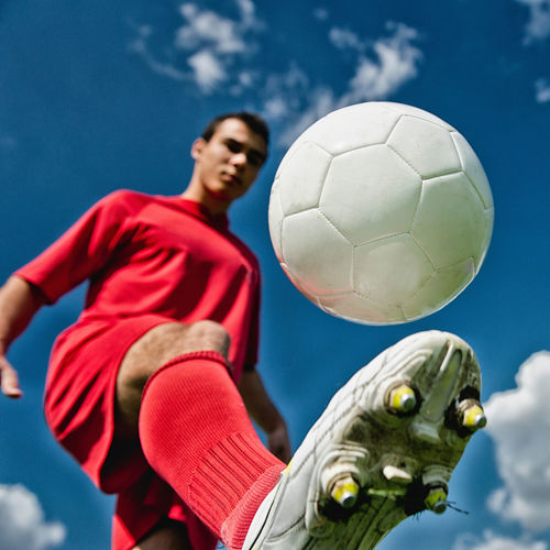 Soccer Player Against Blue Sky, With Ball In Focus Soccer Football Football Player Soccer Player Soccer Ball Ball Soccer Shoe Sports Uniform White Playing Athlete Man Young Outdoors Team Sport Competition One Man Only Championship Strength Copy Space Red Sport One Person Blue Lifestyles