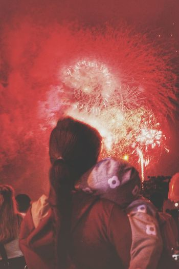 Rear view of people with fire crackers at night