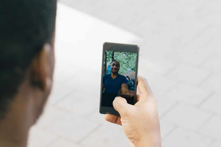 Midsection of person photographing with mobile phone