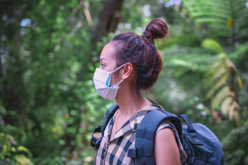 Side view point of young women backpacker wearing surgical mask in rainforest area
