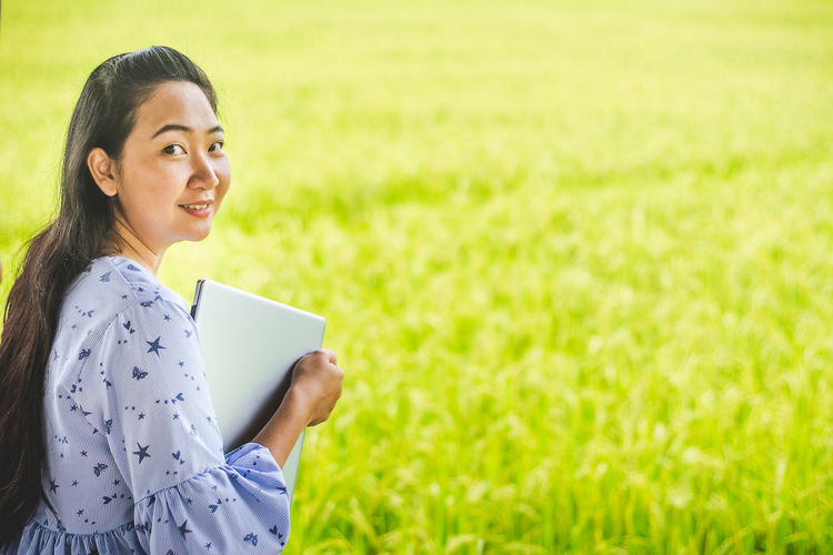 Portrait of woman holding laptop while standing on field