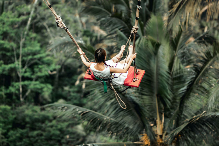 Woman sitting on swing in forest