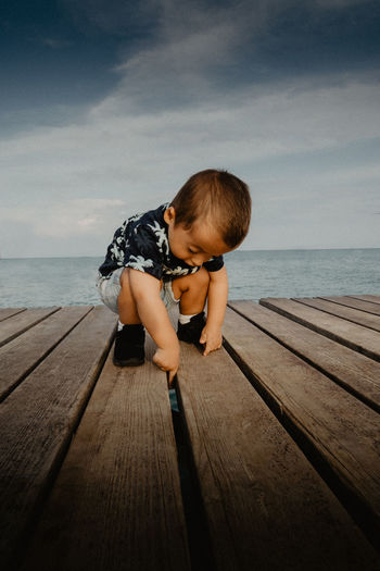 Full length of boy sitting on pier against sea