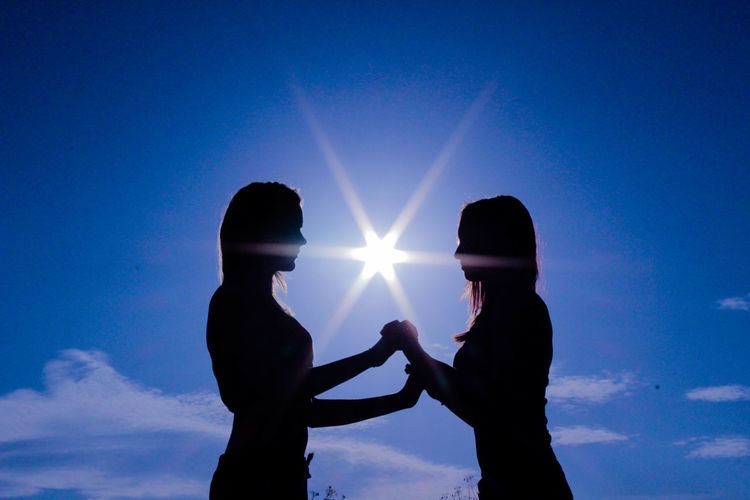 Silhouette lesbian standing against bright sun