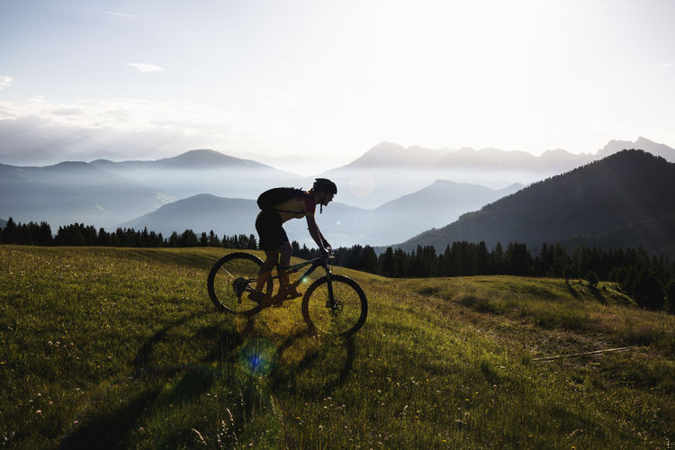 Man riding bicycle on field against sky