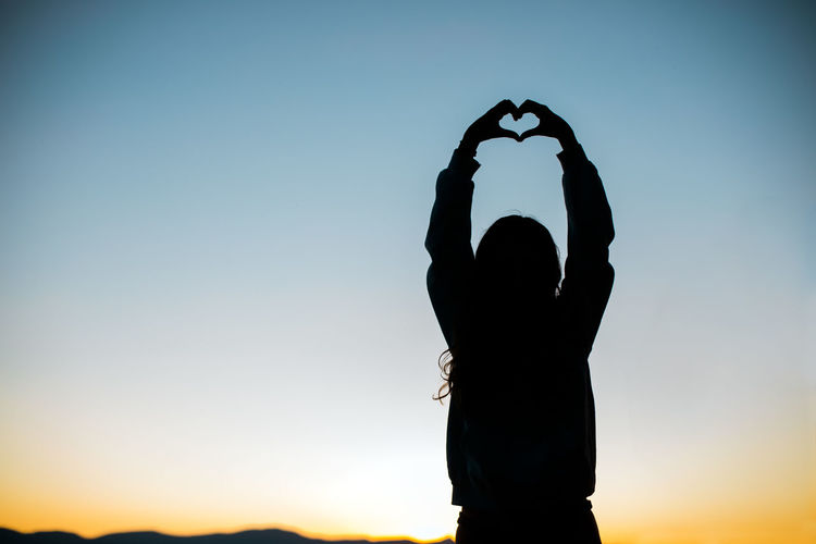 Silhouette woman standing by heart shape against sky during sunset