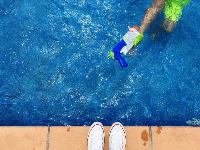High Angle View Of Child With Squirt Gun In Swimming Pool