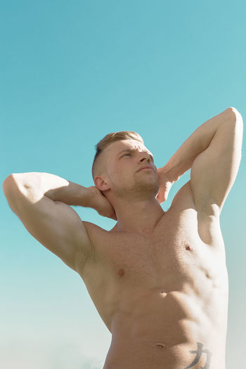 Low Angle View Of Young Man Against Clear Blue Sky