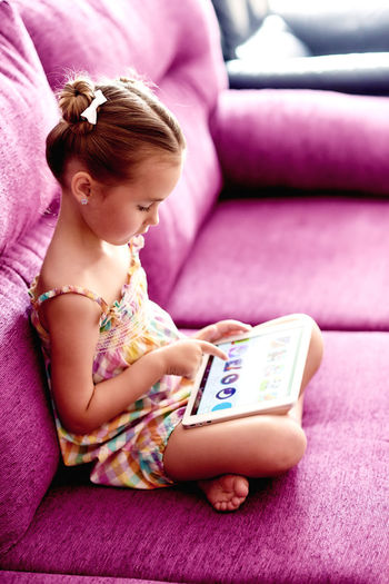 Little pretty girl with a tablet computer on a sofa at home Beautiful Caucasian Child Childhood Cutie Daughter Digital Tablet Entertainment Gadget Game Home Internet Kid Little Girl Looking At Camera Network PC Portrait Pretty Girl Room Small Girl Sofa Tablet Computer Wi Fi Wireless Technology