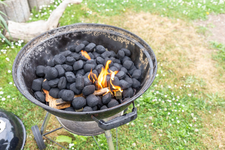 High angle view of bonfire on barbecue grill in yard
