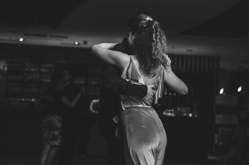 Close-up of couple dancing in darkroom