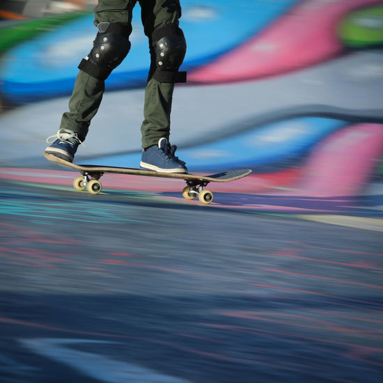 Low section of person skateboarding on water