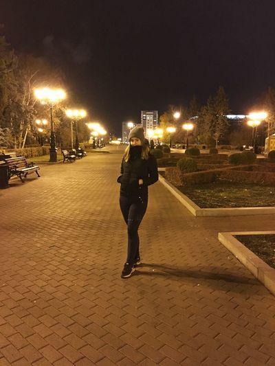 Full length of woman on illuminated street at night