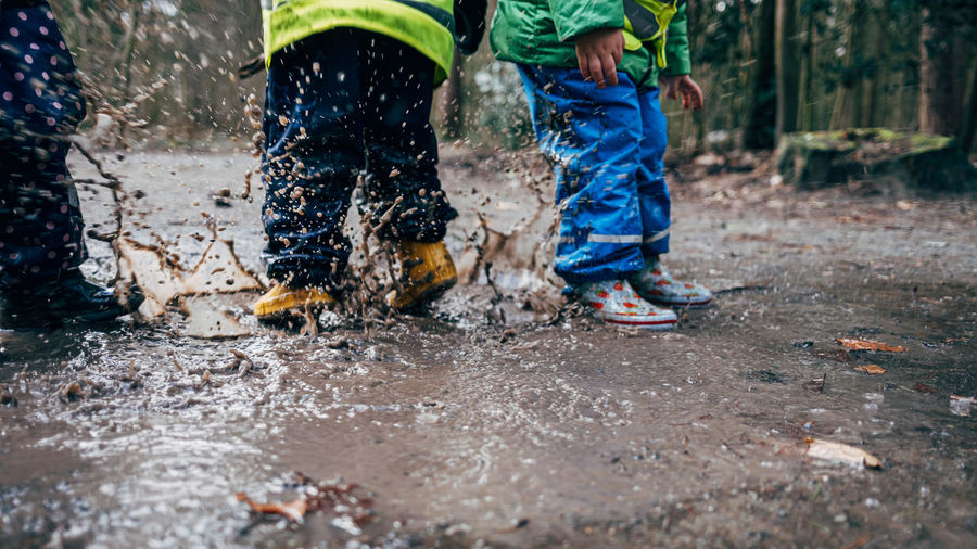 Lower section of children playing in puddle
