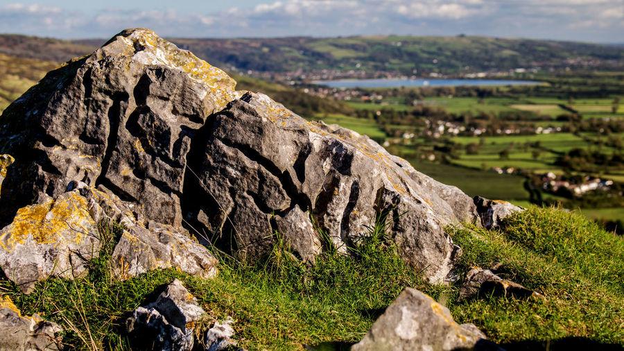Close-up of rock on landscape against sky