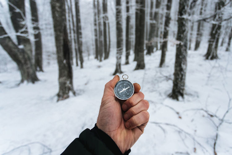 Cropped hand holding navigational compass