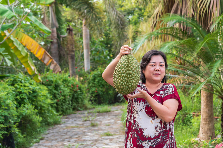 Portrait of mature woman holding durian while standing on footpath amidst plants