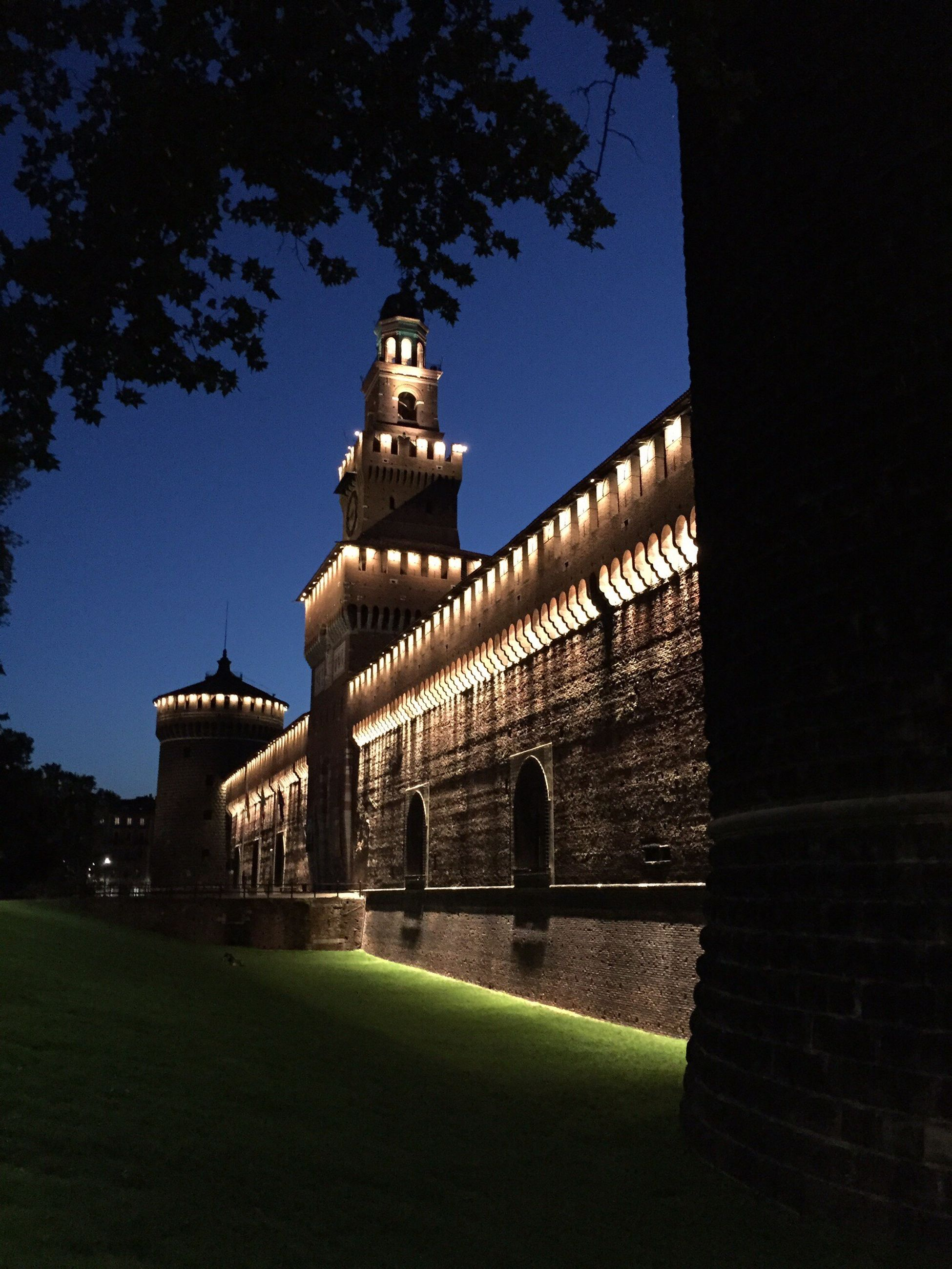 architecture, built structure, building exterior, clear sky, tree, history, night, famous place, outdoors, travel destinations, grass, exterior, low angle view, place of worship, copy space, green color, sky, castle, arch, illuminated