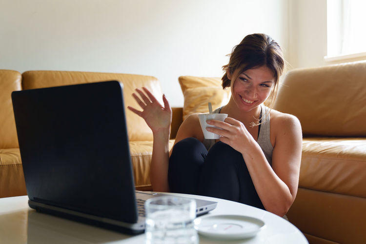Young woman using mobile phone while sitting on sofa