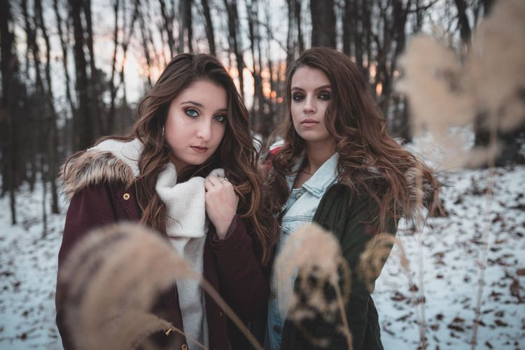 Winter Cold Temperature Long Hair Young Adult Two People Snow Front View Outdoors Beautiful Woman Warm Clothing Portrait Looking At Camera Lifestyles Standing Friendship Tree Trunk